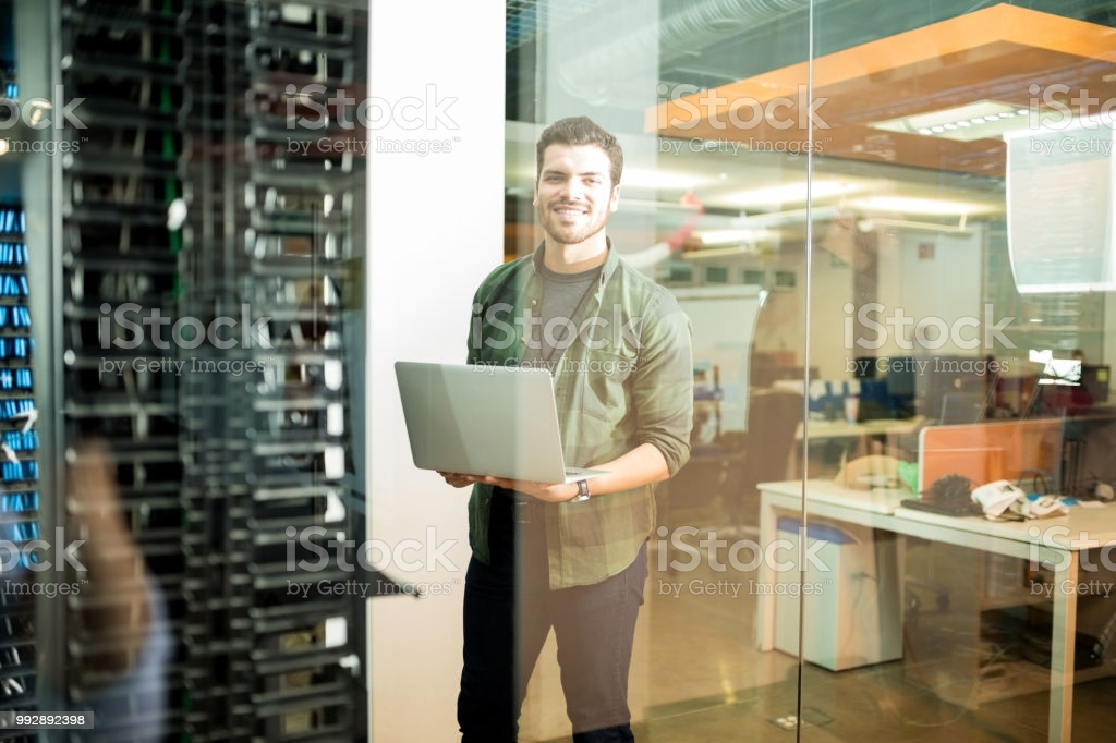 Portrait of happy male technician with laptop in large data center