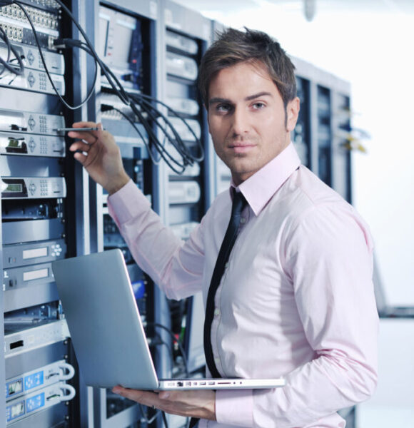 Businessman with a laptop working in a network server room